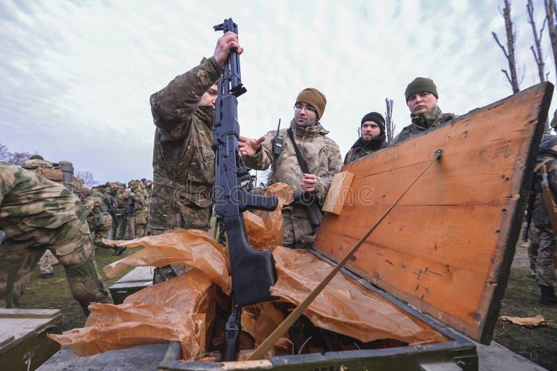 O homem retira a arma da caixa militar imagens de stock