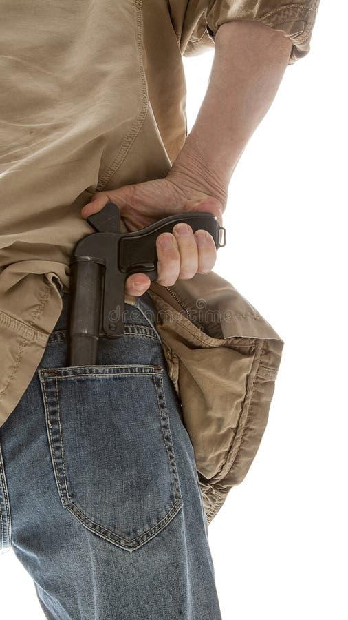 O homem retira uma arma do seu para trás fotografia de stock royalty free