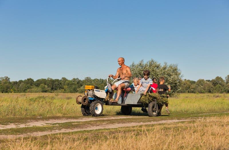 O homem rola crianças em um mini trator em Koncha-Zaspa, Ucrânia foto de stock