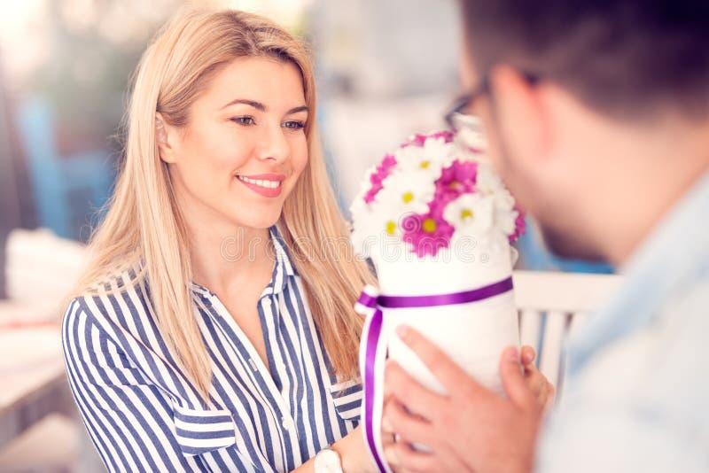O homem romântico dá um arranjo de flor a sua amiga fotografia de stock