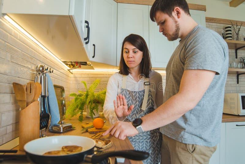 O homem roubar o alimento quando mulher que faz o café da manhã foto de stock