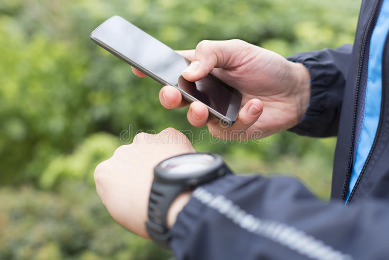 O homem running com telefone celular conectou a um relógio esperto fim imagens de stock
