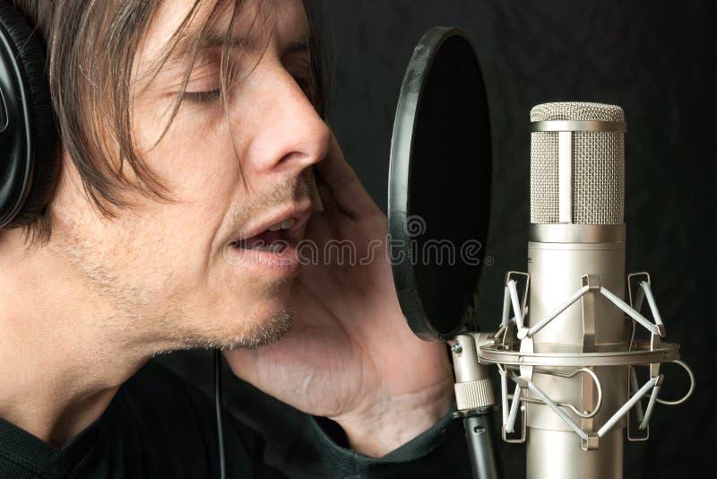 O homem sério grava Vocals em Stuio fotos de stock