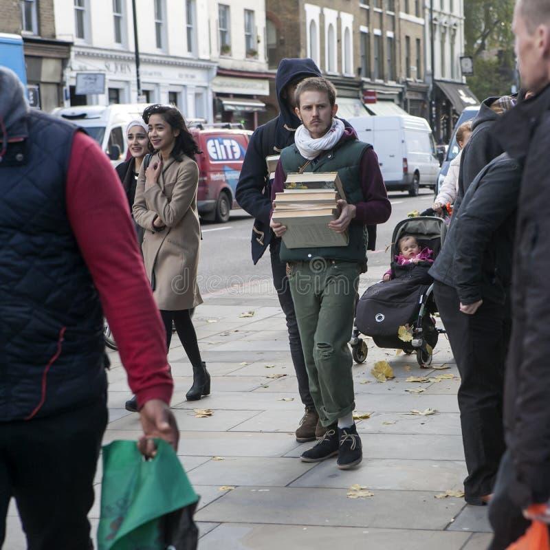 O homem sério leva uma pilha de livros na pista do tijolo foto de stock royalty free