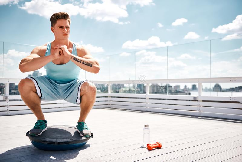 O homem sério squatting na plataforma de BOSU no balcão alto imagem de stock royalty free