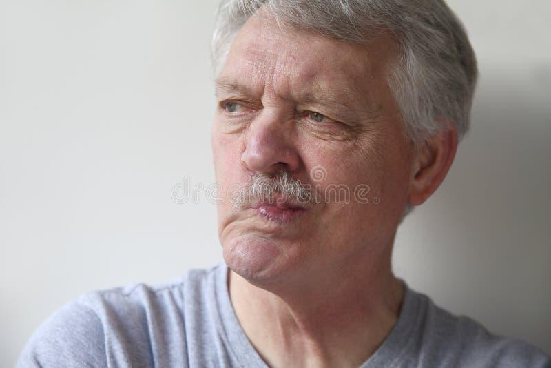 O homem sênior distorce sua boca foto de stock royalty free