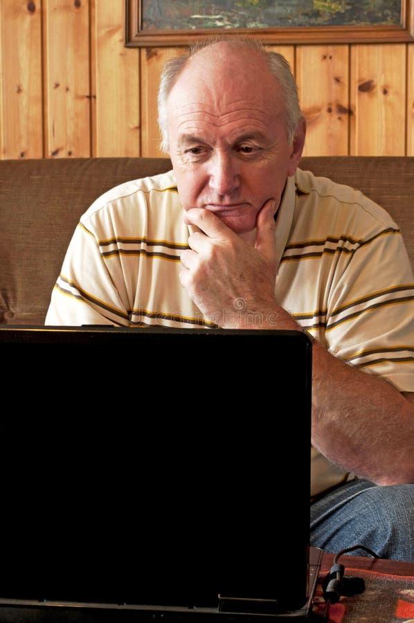 O homem sênior está trabalhando no portátil fotos de stock royalty free