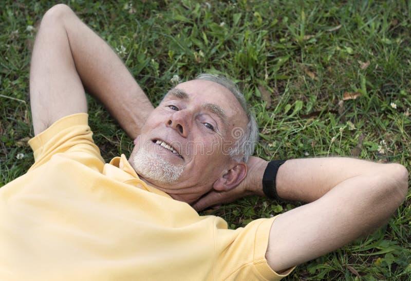 O homem sênior que encontra-se na grama satisfêz foto de stock