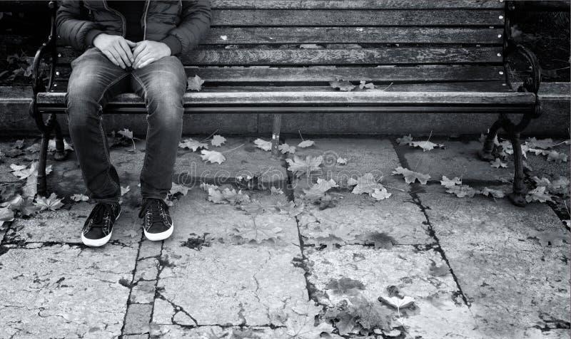 O homem só senta-se em um banco de madeira imagens de stock
