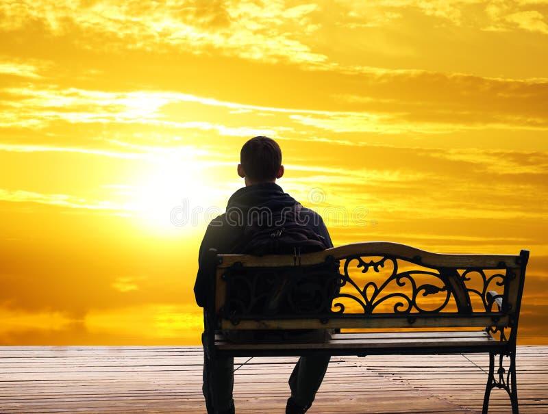 O homem só senta-se em uma diminuição foto de stock