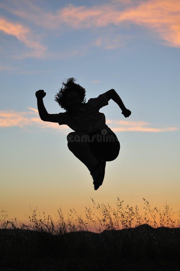 O homem salta altamente na frente do por do sol fotografia de stock