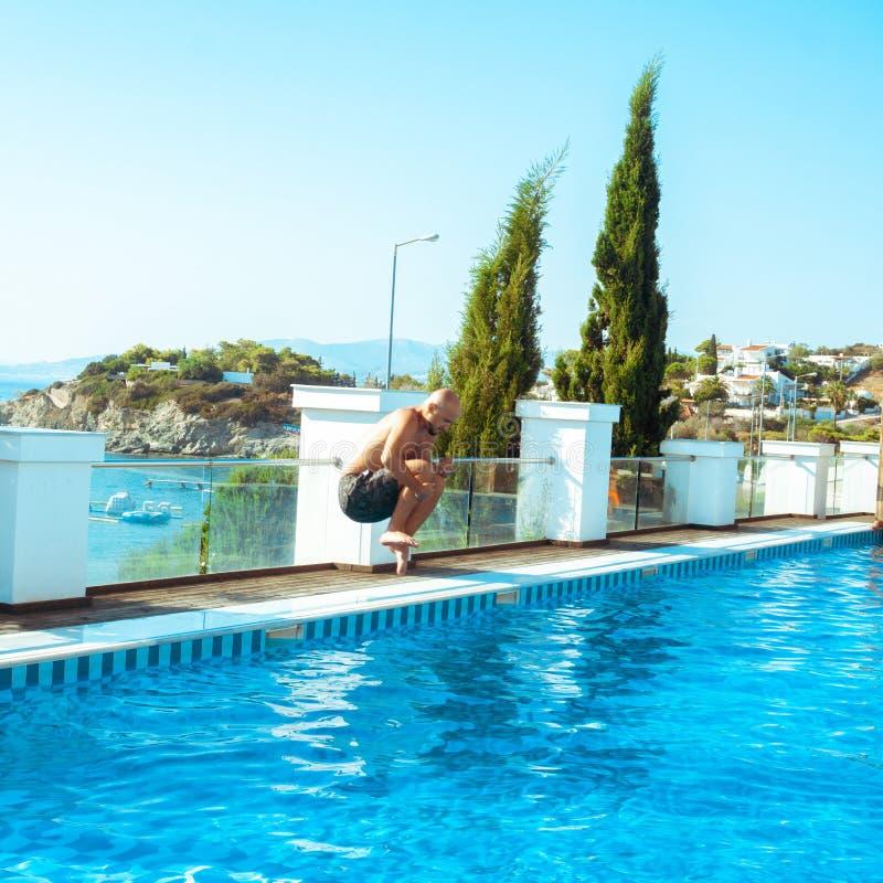 O homem salta no swimpool fotos de stock