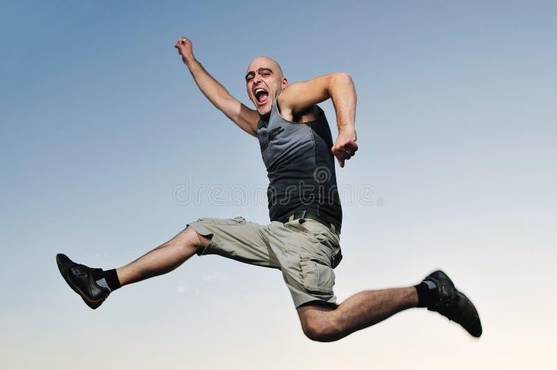 O homem salta o por do sol ao ar livre imagem de stock royalty free