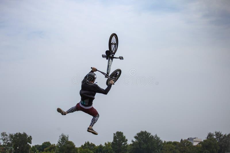 O homem salta uma bicicleta na água de um cais Belgorod, Rússia - 25 DE JULHO DE 2019 foto de stock royalty free
