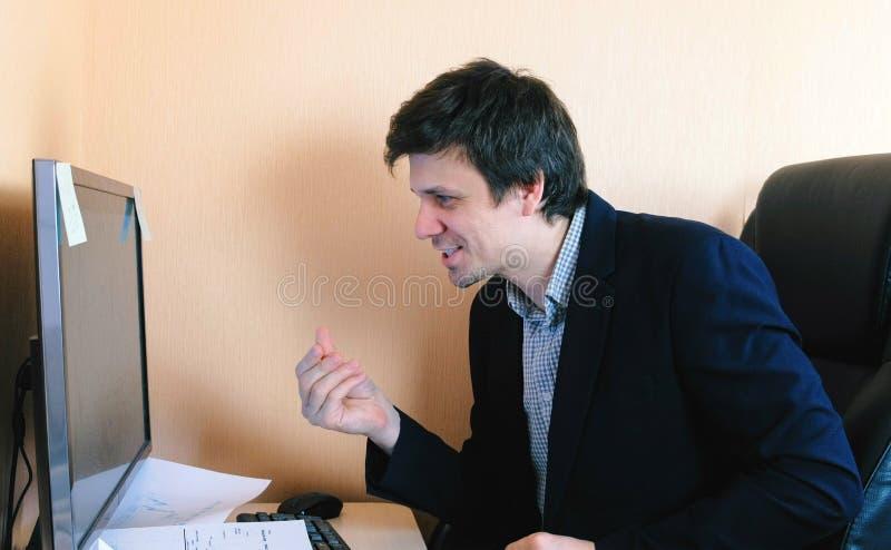 O homem satisfeito fricciona suas mãos que sentam-se no computador Trabalho no computador fotos de stock