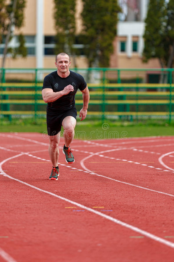 O homem saudável corre na trilha do esporte da raça do atletismo e c da representação imagens de stock