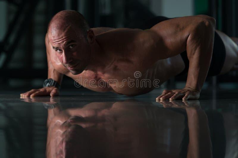 O homem saudável que faz a imprensa levanta no Gym imagens de stock royalty free