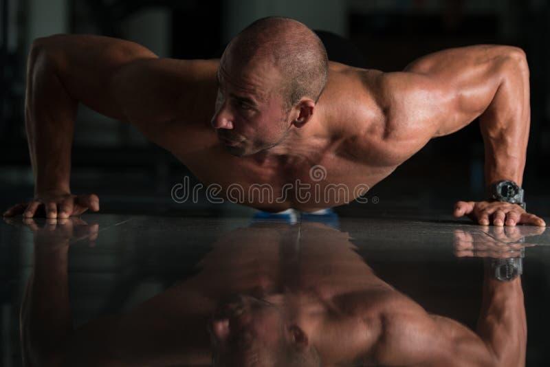 O homem saudável que faz a imprensa levanta no Gym fotografia de stock royalty free