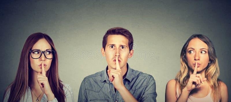 O homem secreto dos jovens e duas mulheres com o dedo aos bordos gesticulam foto de stock