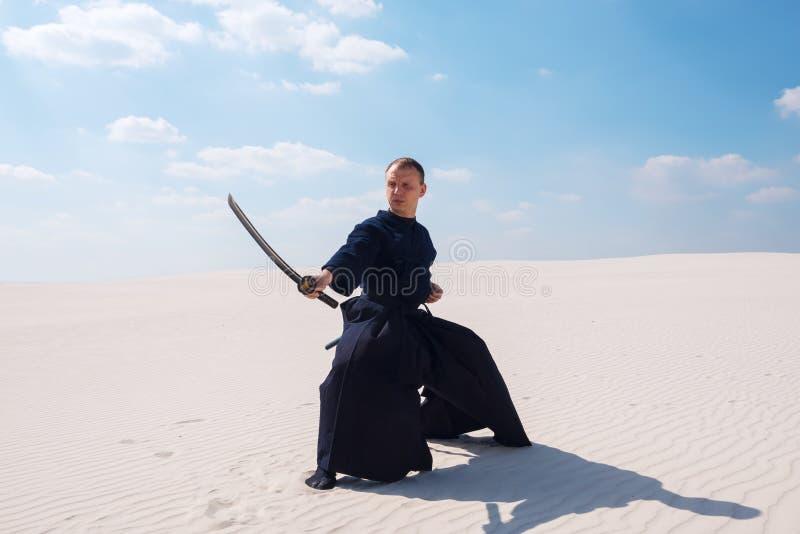 O homem seguro com uma espada em suas mãos está na baixa posição foto de stock royalty free