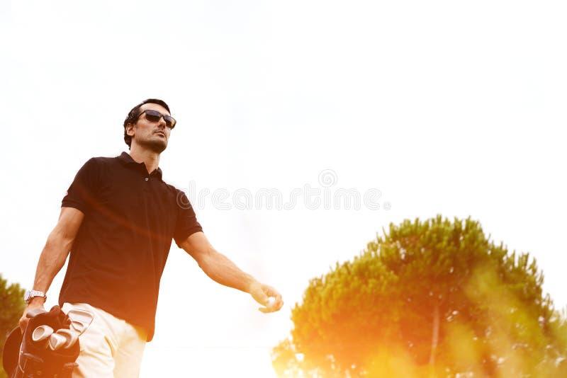 O homem seguro rico bonito passa seus fins de semana no campo de golfe Esporte para homens ricos fotos de stock