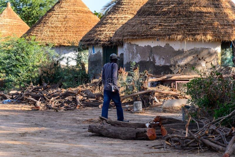 O homem senegalês não identificado anda na frente das barracas em Djo foto de stock