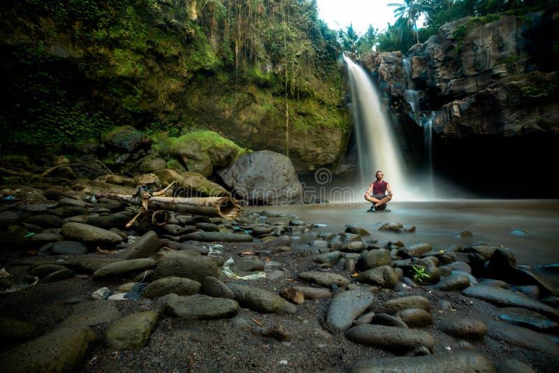 O homem senta equipado com pernas transversal em rochas abaixo da cachoeira fotos de stock royalty free