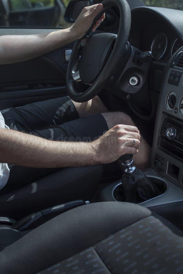 O homem senta-se atrás da roda de um automóvel de passageiros e puxa-se o handbrake fotos de stock royalty free