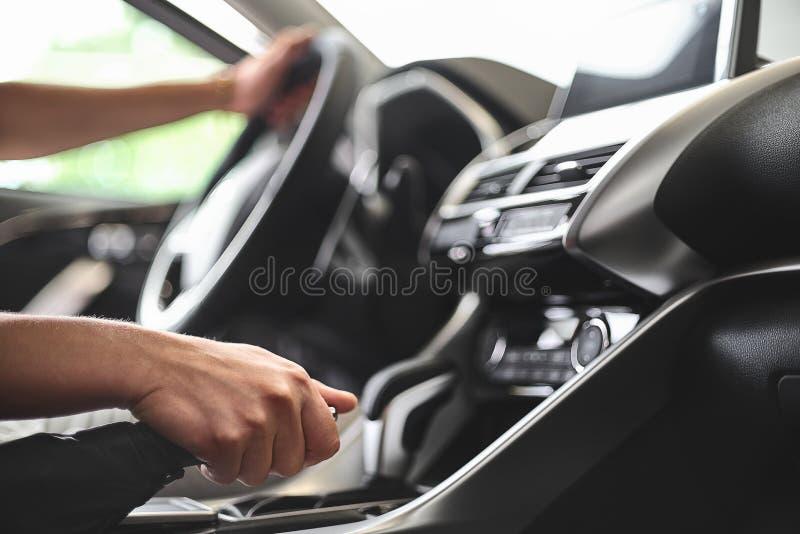 O homem senta-se atrás da roda de um automóvel de passageiros e puxa-se o handbrake foto de stock