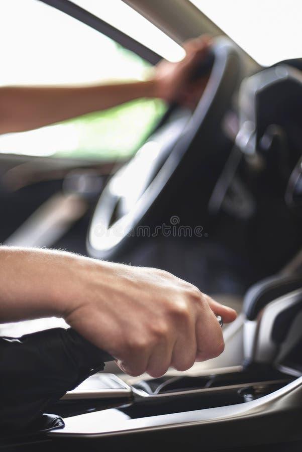 O homem senta-se atrás da roda de um automóvel de passageiros e puxa-se o handbrake fotos de stock