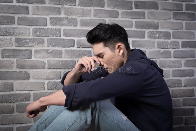 O homem senta-se e sente-se deprimido imagem de stock