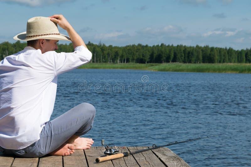 O homem senta-se em um cais de madeira para a pesca usando o gerencio no rio imagem de stock