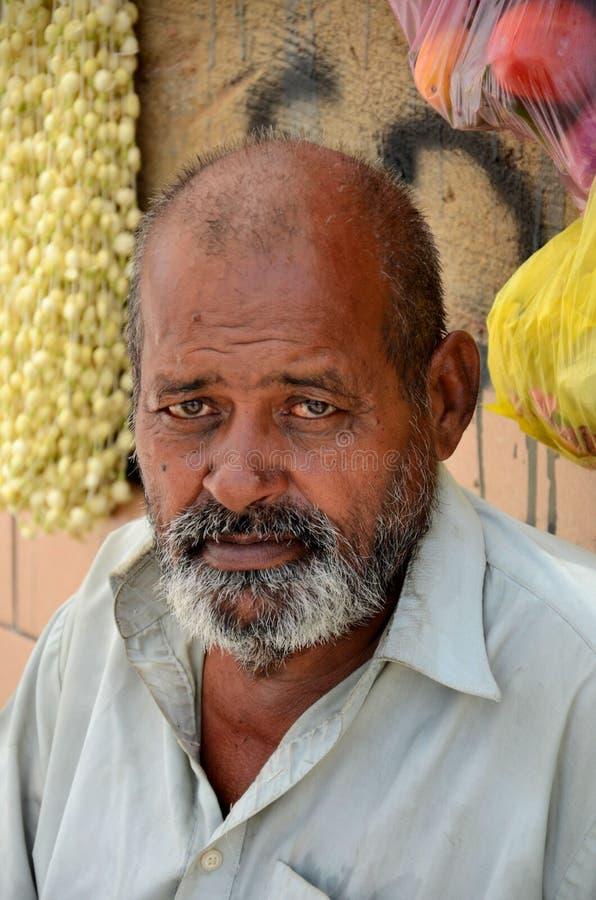 O homem senta-se fora do cemitério cristão que vende as pétalas e as ofertas Karachi Paquistão da festão foto de stock royalty free