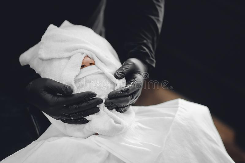 O homem senta-se na cadeira do barbeiro e cozinha-se sua cara com a toalha quente na frente da barba real que barbeia a lâmina fotos de stock royalty free