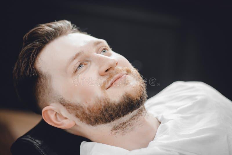 O homem senta-se na cadeira do barbeiro e cozinha-se sua cara com a toalha quente na frente da barba real que barbeia a lâmina fotografia de stock