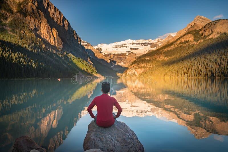 O homem senta-se na rocha que olha reflexões de Lake Louise imagens de stock