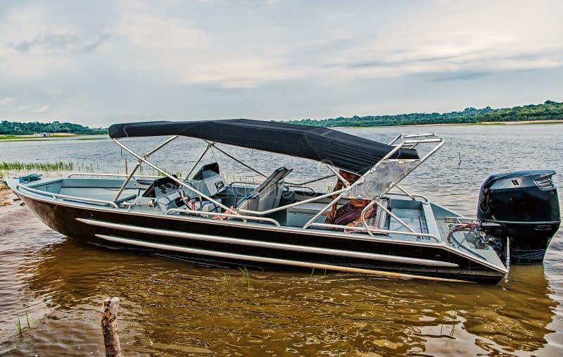 O homem senta-se no barco de motor ou no powerboat amarrado na costa de mar em manaus, Brasil Transporte e embarcação da água Fér fotografia de stock royalty free