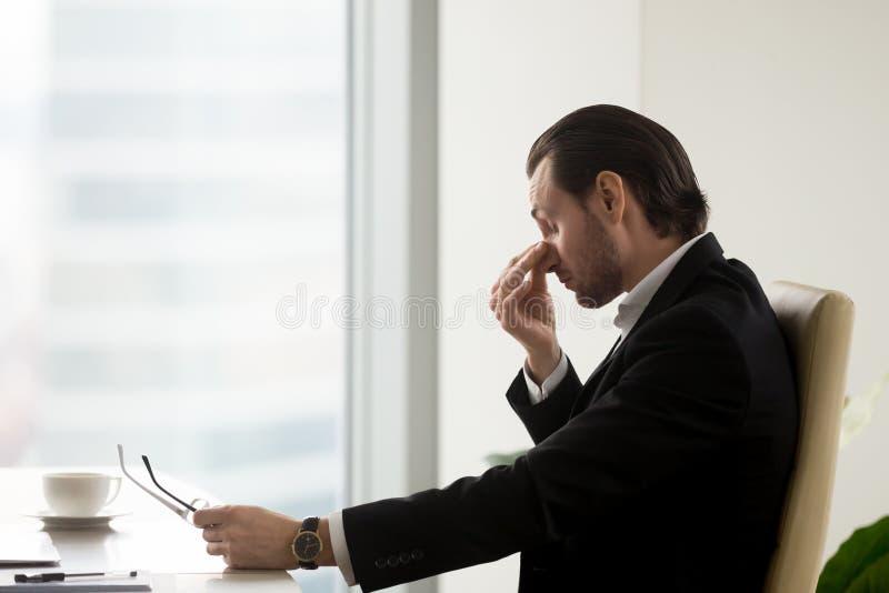 O homem sente a fadiga nos olhos após o trabalho no escritório imagem de stock