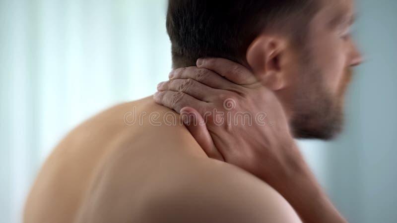 O homem sente que dor de pescoço após acordou na manhã, matrass incômodos, close up imagens de stock