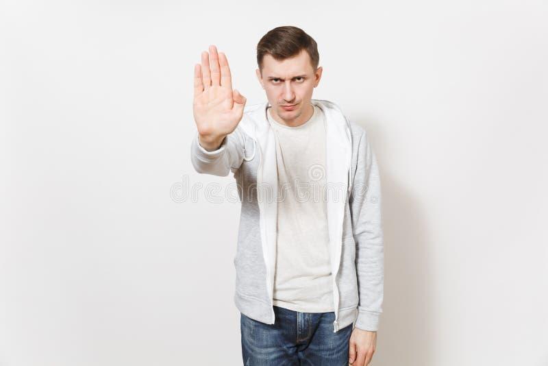 O homem severo sério novo no t-shirt, na calças de ganga e no gesto claro da parada da exibição da camiseta com palma, olha de so imagem de stock royalty free