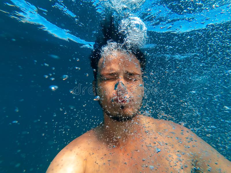 O homem sob a água afunda-se para assentar-se e libera-se bolhas do oxigênio foto de stock royalty free
