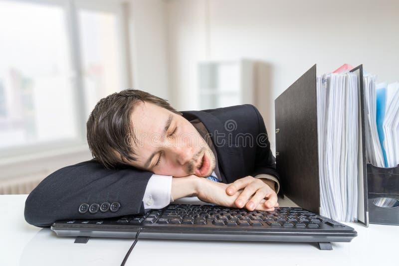 O homem sobrecarregado cansado está dormindo no teclado no escritório no trabalho foto de stock