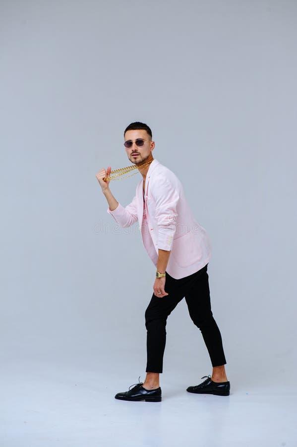 O homem sofisticado elegante em um revestimento cor-de-rosa e em uma calças preta, veste uma corrente do ouro, a expressão das em fotografia de stock