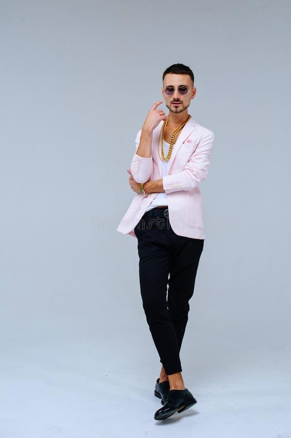 O homem sofisticado elegante em um revestimento cor-de-rosa e em uma calças preta, veste uma corrente do ouro, a expressão das em imagens de stock royalty free