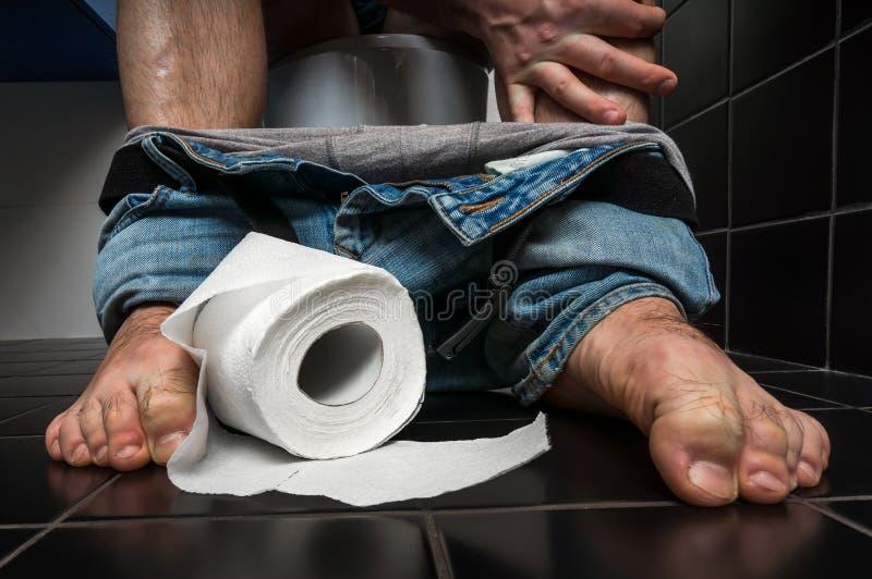 O homem sofre da diarreia está sentando-se na bacia de toalete foto de stock
