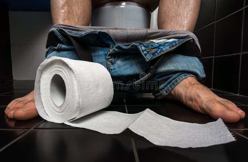 O homem sofre da diarreia está sentando-se na bacia de toalete imagens de stock royalty free