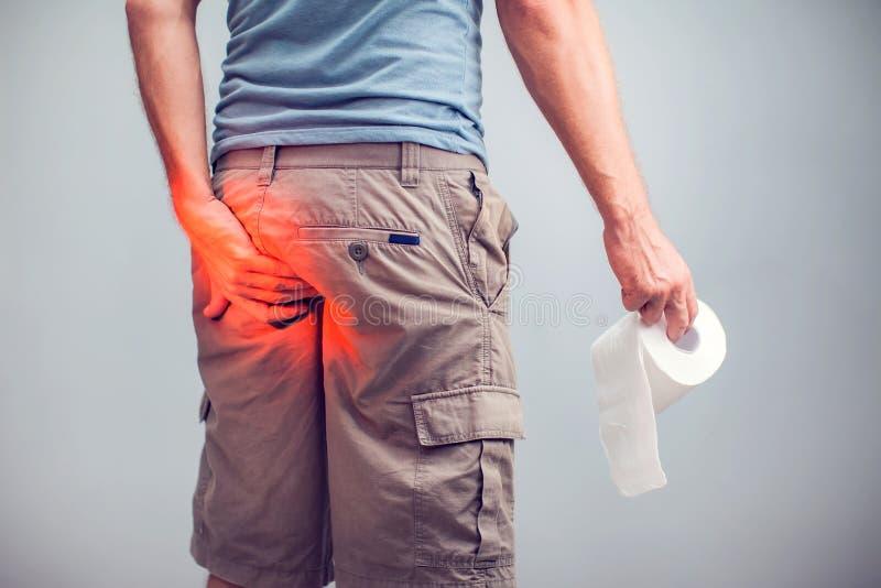 O homem sofre da diarreia guarda o rolo do papel higiênico O indivíduo é ho imagens de stock