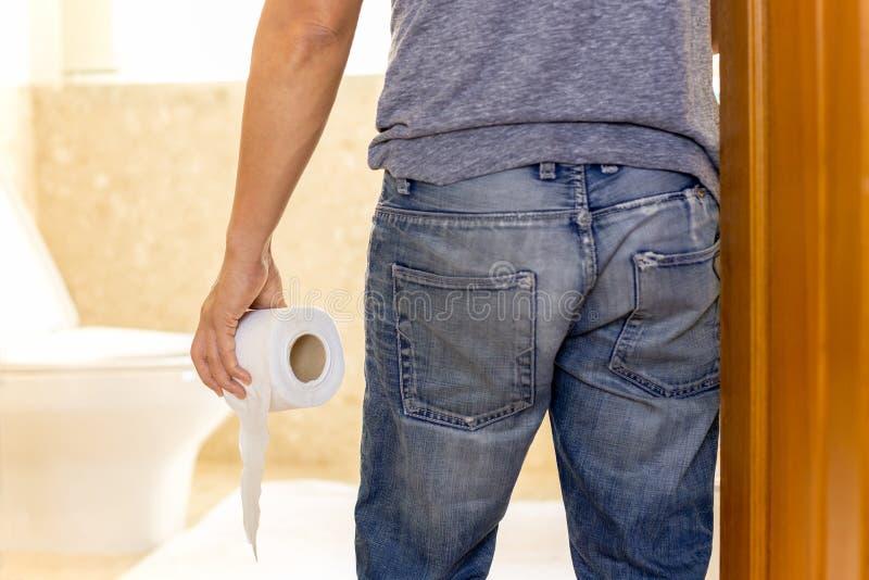 O homem sofre da diarreia que guarda o rolo do papel higiênico para ir ao toalete imagens de stock royalty free
