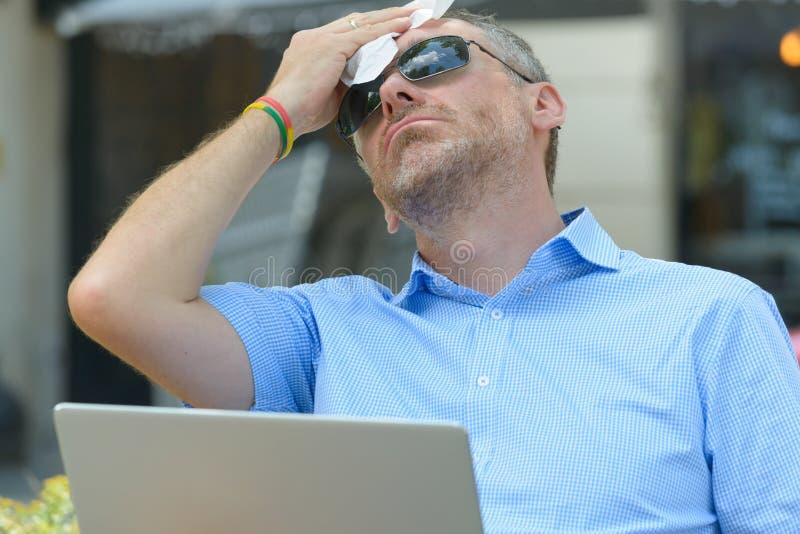 O homem sofre do calor ao trabalhar com portátil fotografia de stock