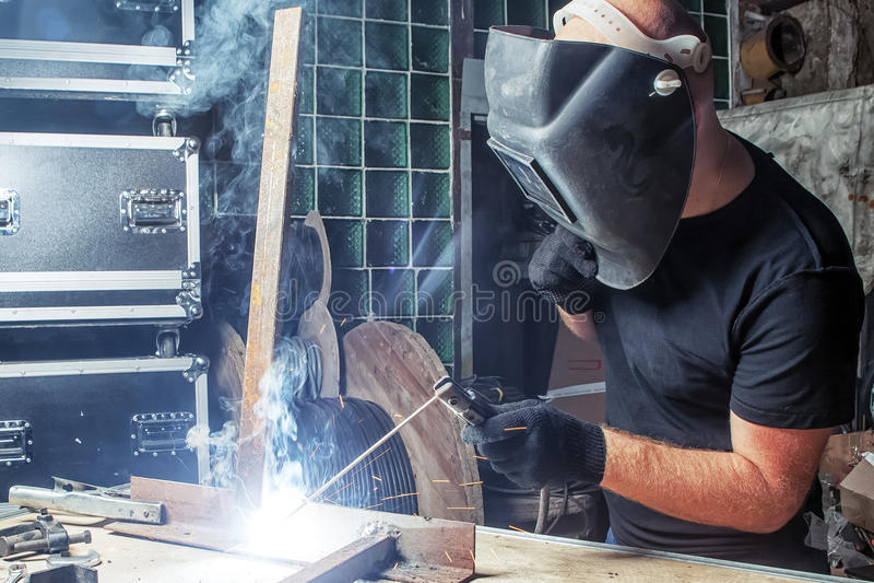 O homem solda uma máquina de soldadura do arco do metal fotografia de stock royalty free